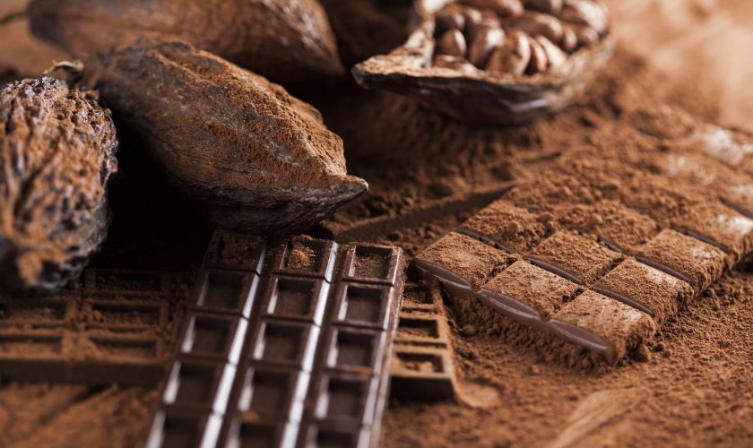 Dark homemade chocolate bars and cocoa pod on wooden